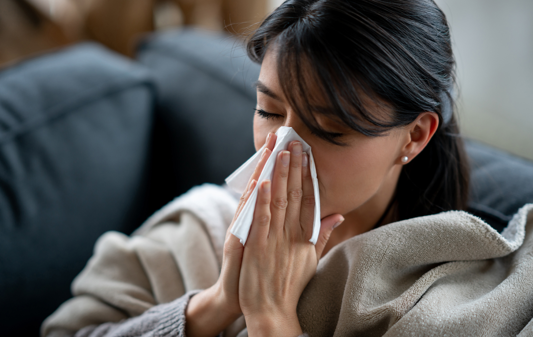 Woman sneezing with a tissue