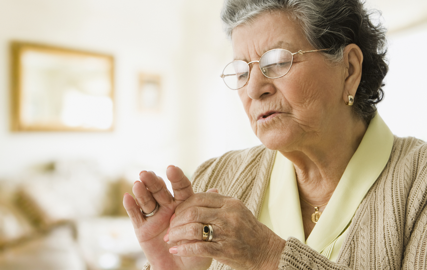 AltaMEd older women gripping her hands arthritis