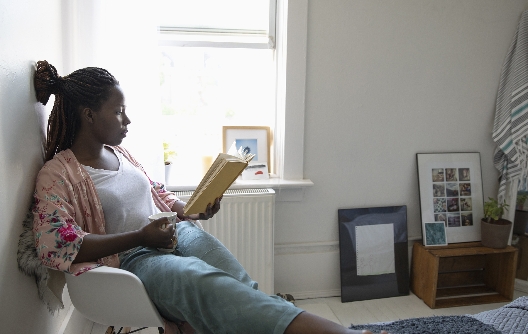 mujer afroamericana leyendo en una esquina de su casa