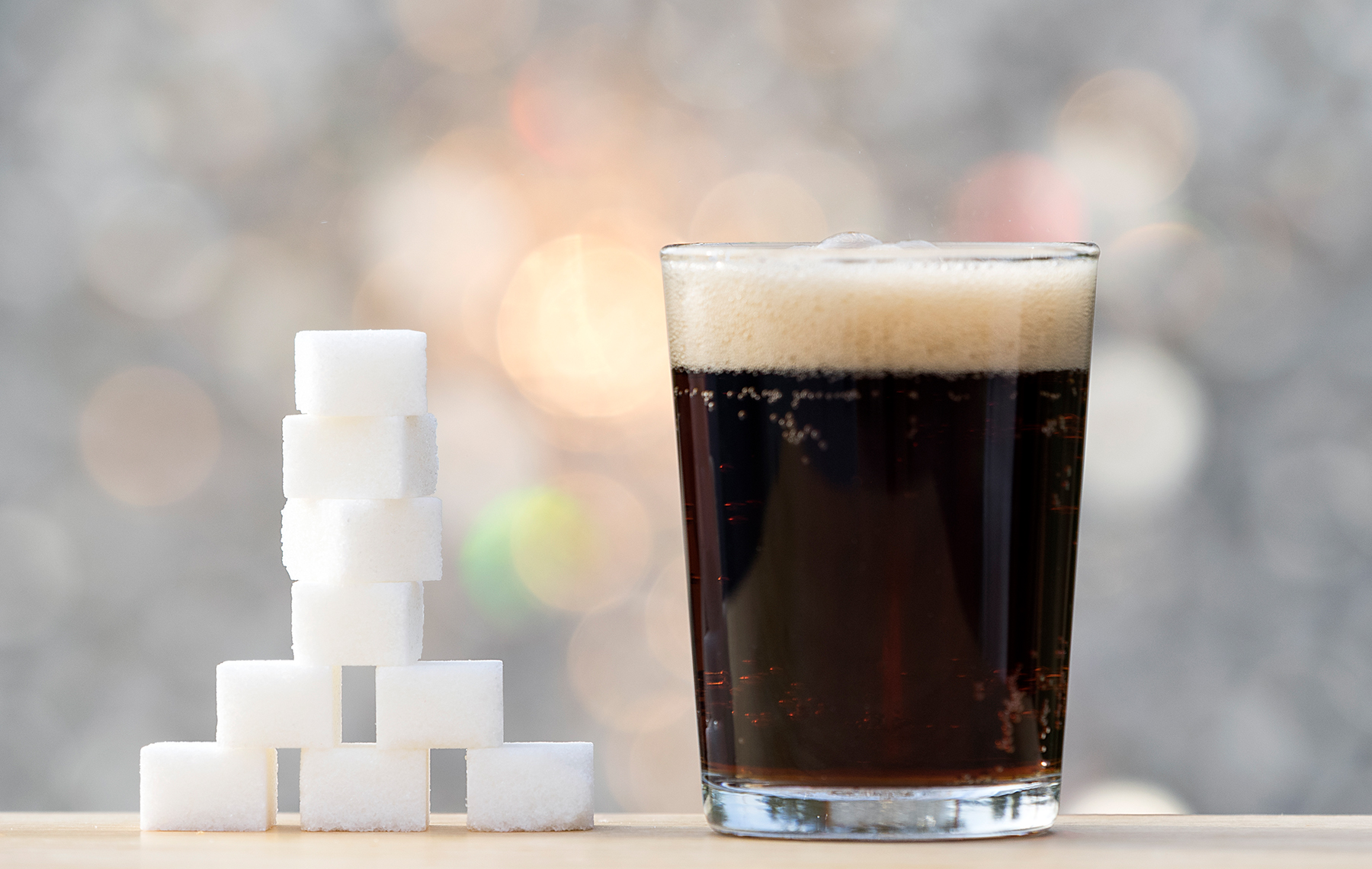 A glass of soda and on the side sugar cubes