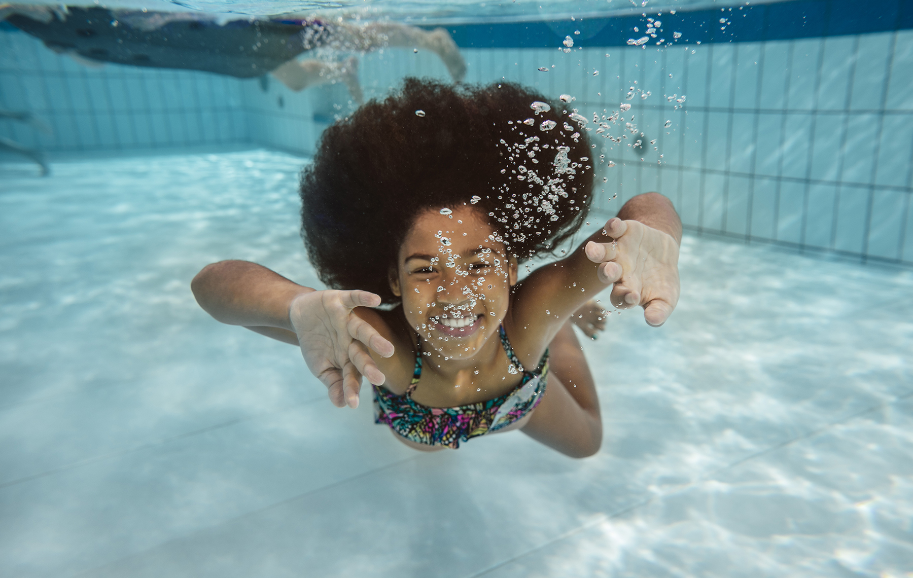 AltaMed little girl swimming under water