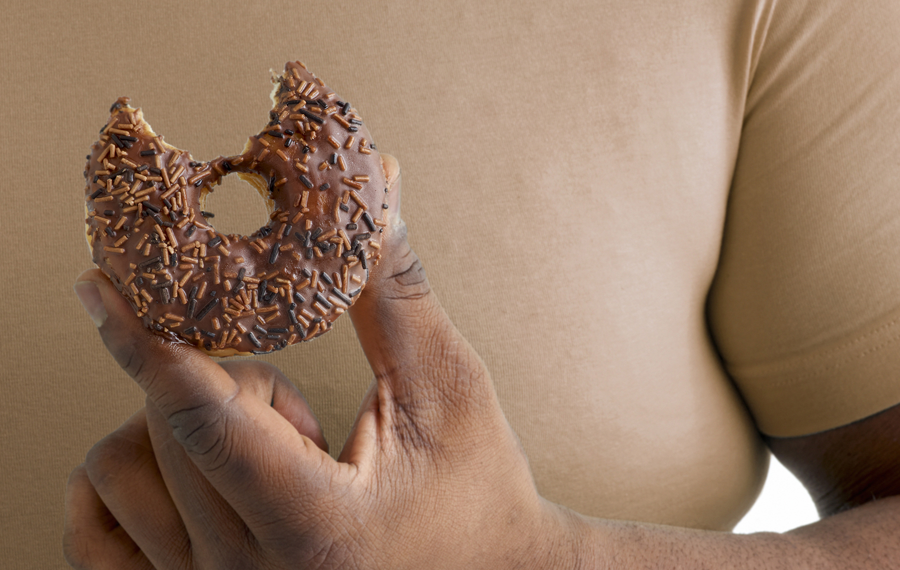 AltaMed person holding a chocolate doughnut