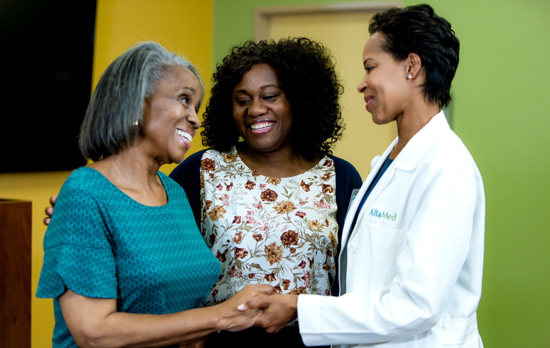 Doctor and nurse talking to a senior woman