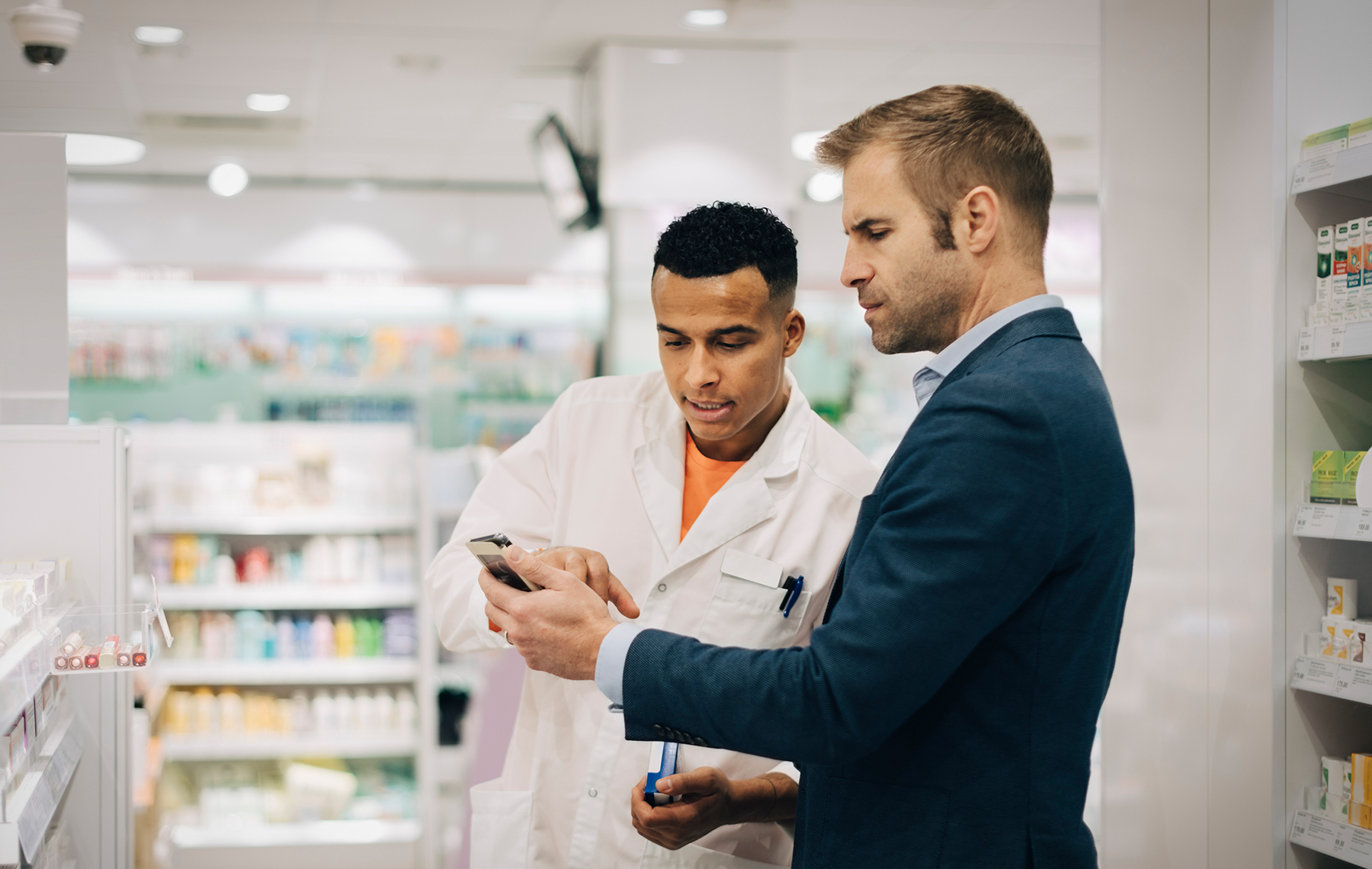 Pharmacist and a client looking at a celphone