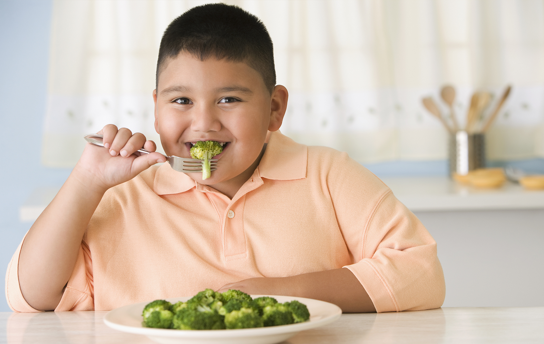 chubby child eating broccoli
