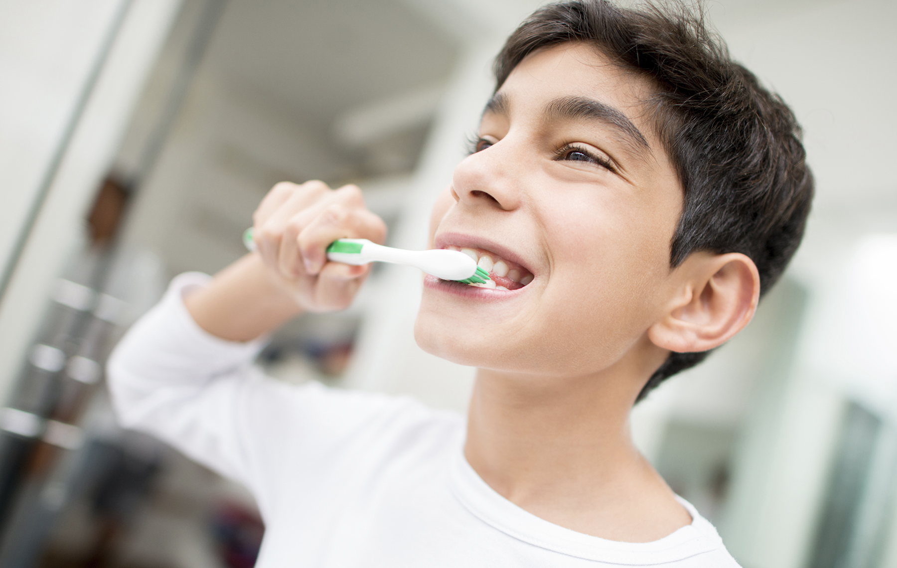 AltaMed tween boy in white shirt brushing teeth