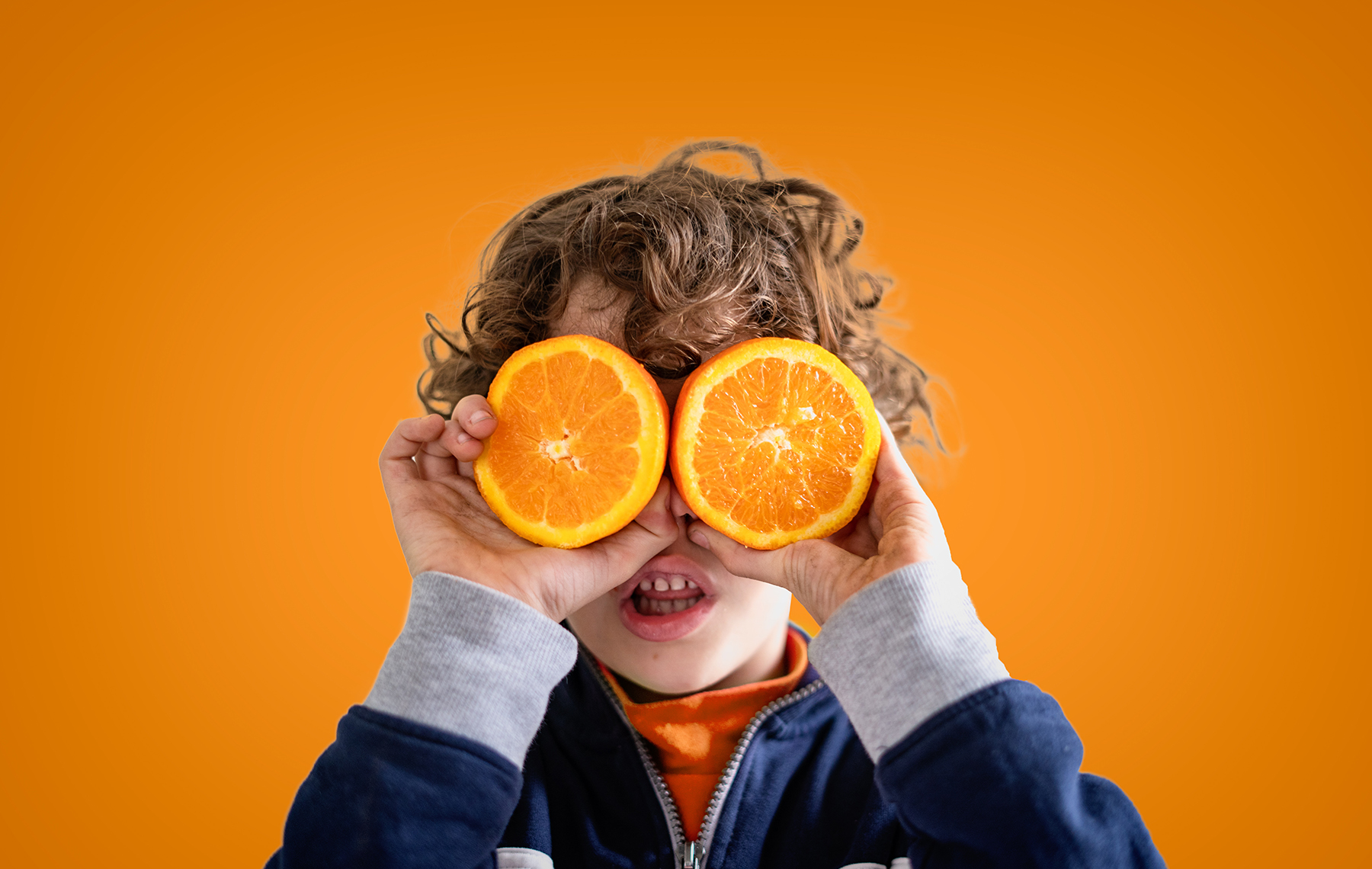 Kid holding oranges in front of his eyes