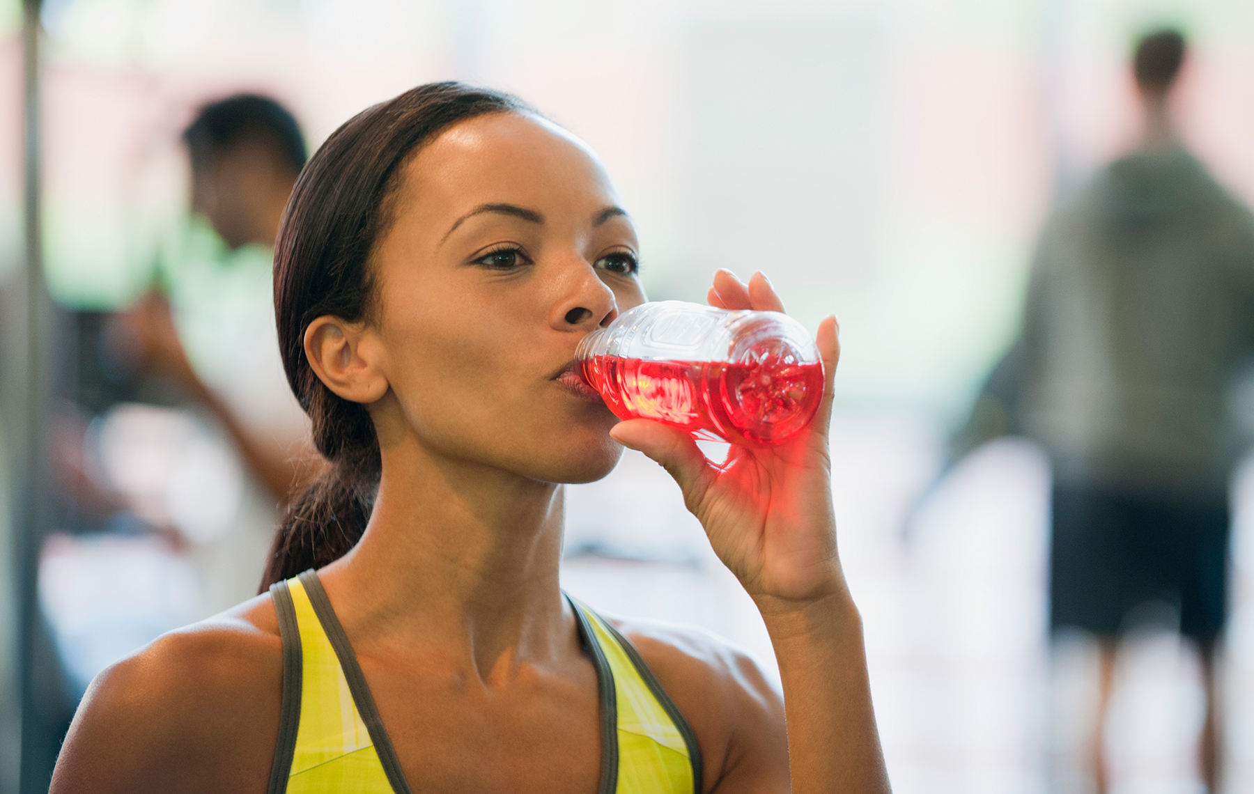Sport woman drink a red sport drink