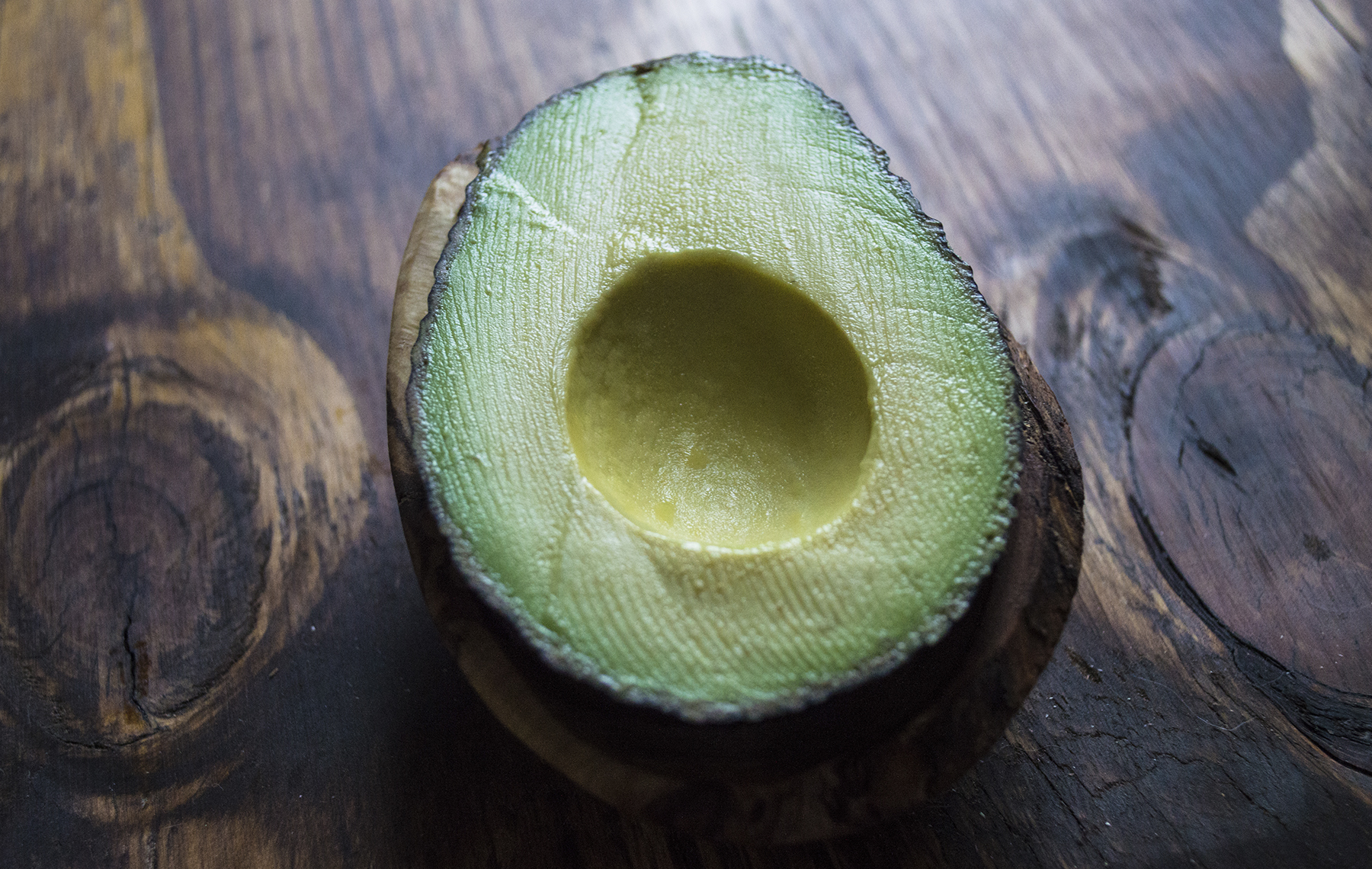 AltaMed half avocado on wooden table