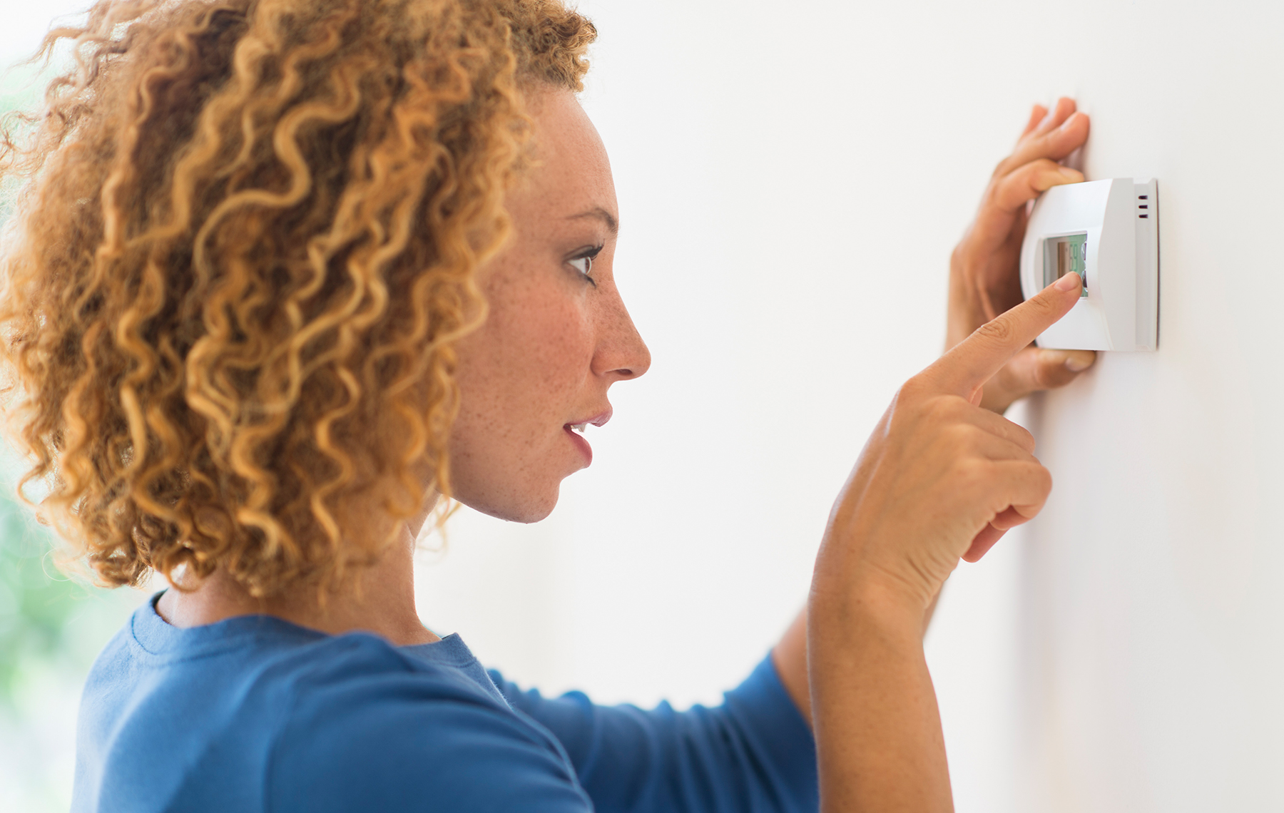AltaMed woman changing thermostat