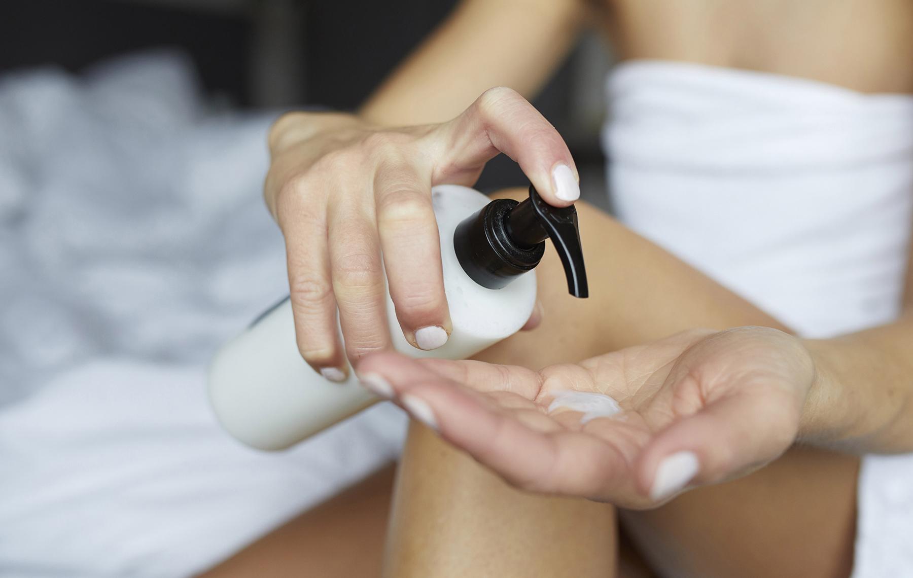 Woman Putting Moisturizing Cream On Her Hand