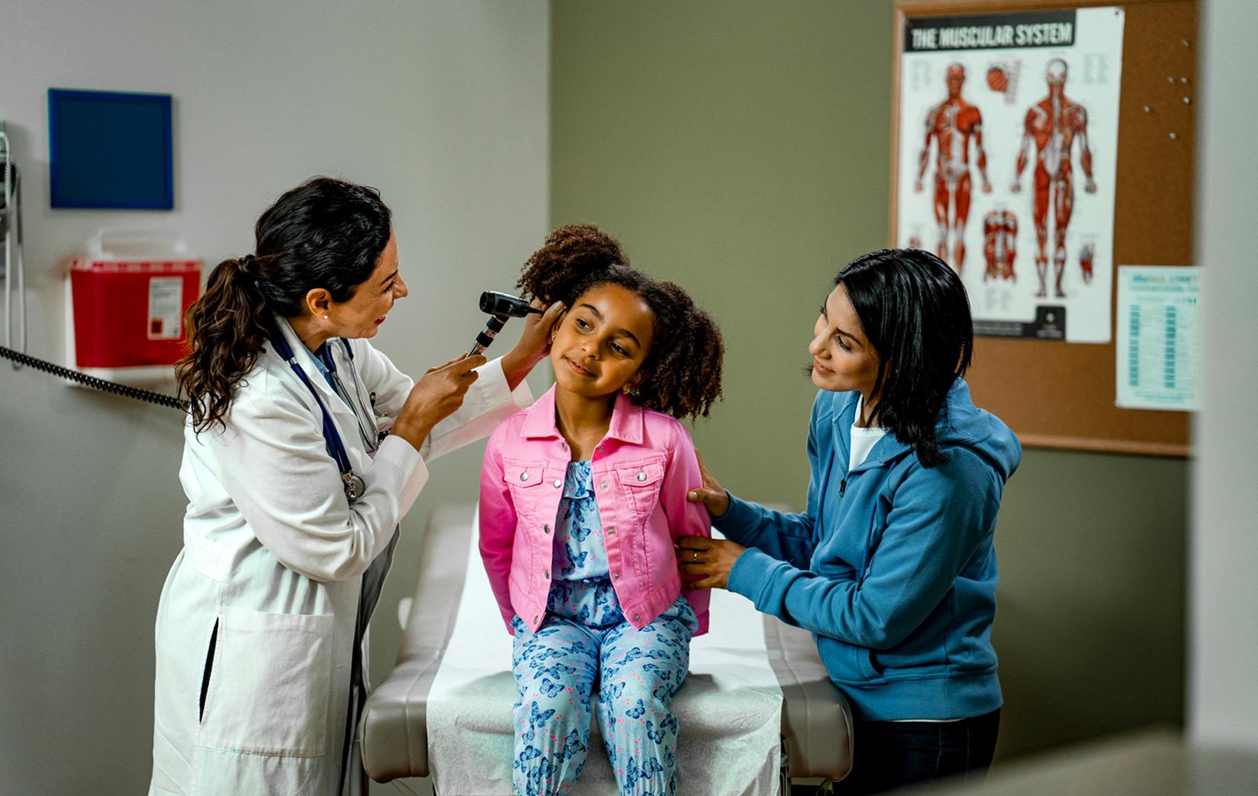Pediatra revisando el oído de una niña