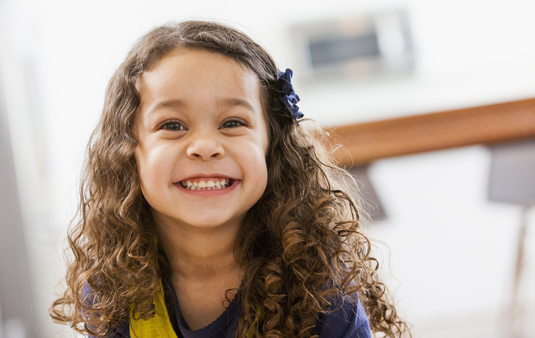 AltaMed Small girl with curls smiling showing teeth