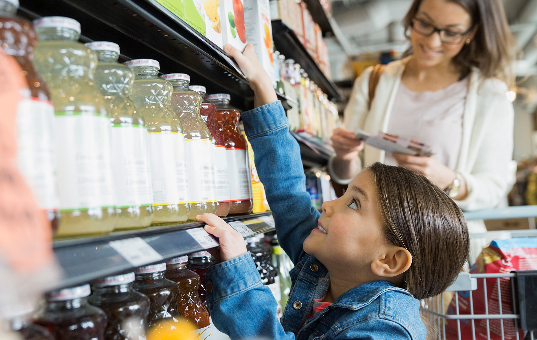 Child trying to reach a juice in the supermarket
