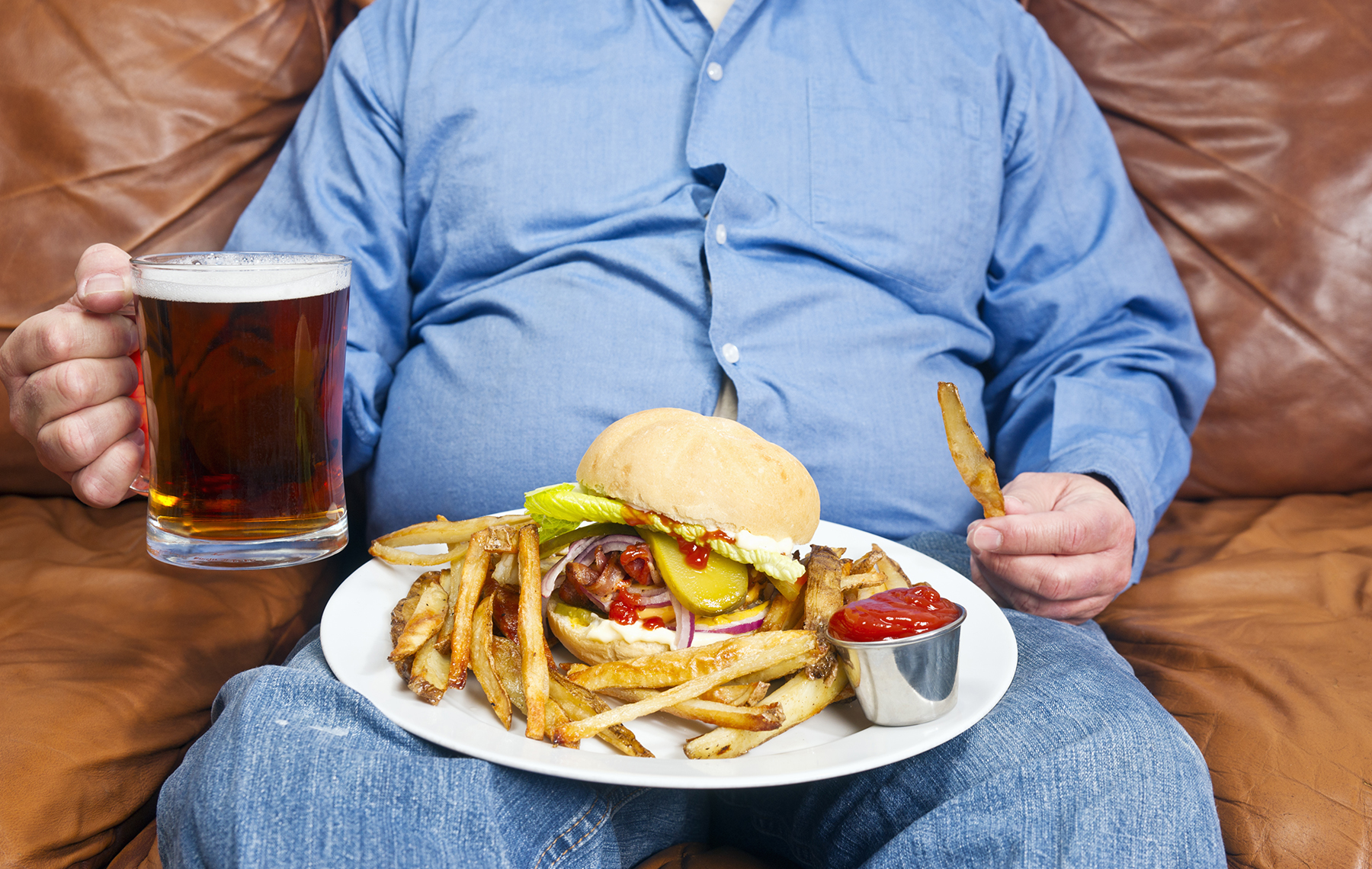 AltaMed chubby man sitting on couch with burger fries and beer