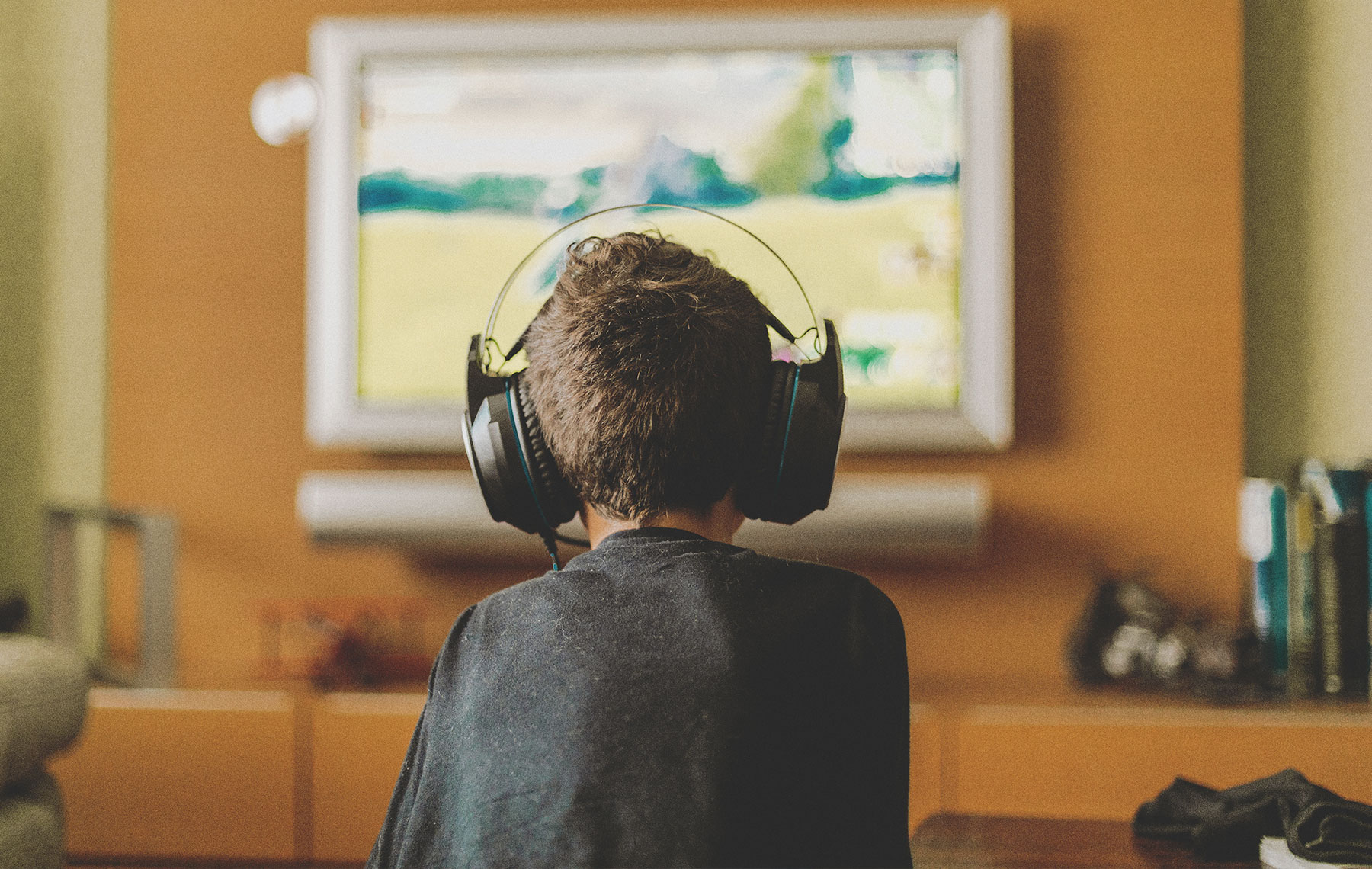 back of a kid watching tv and wearing headphones