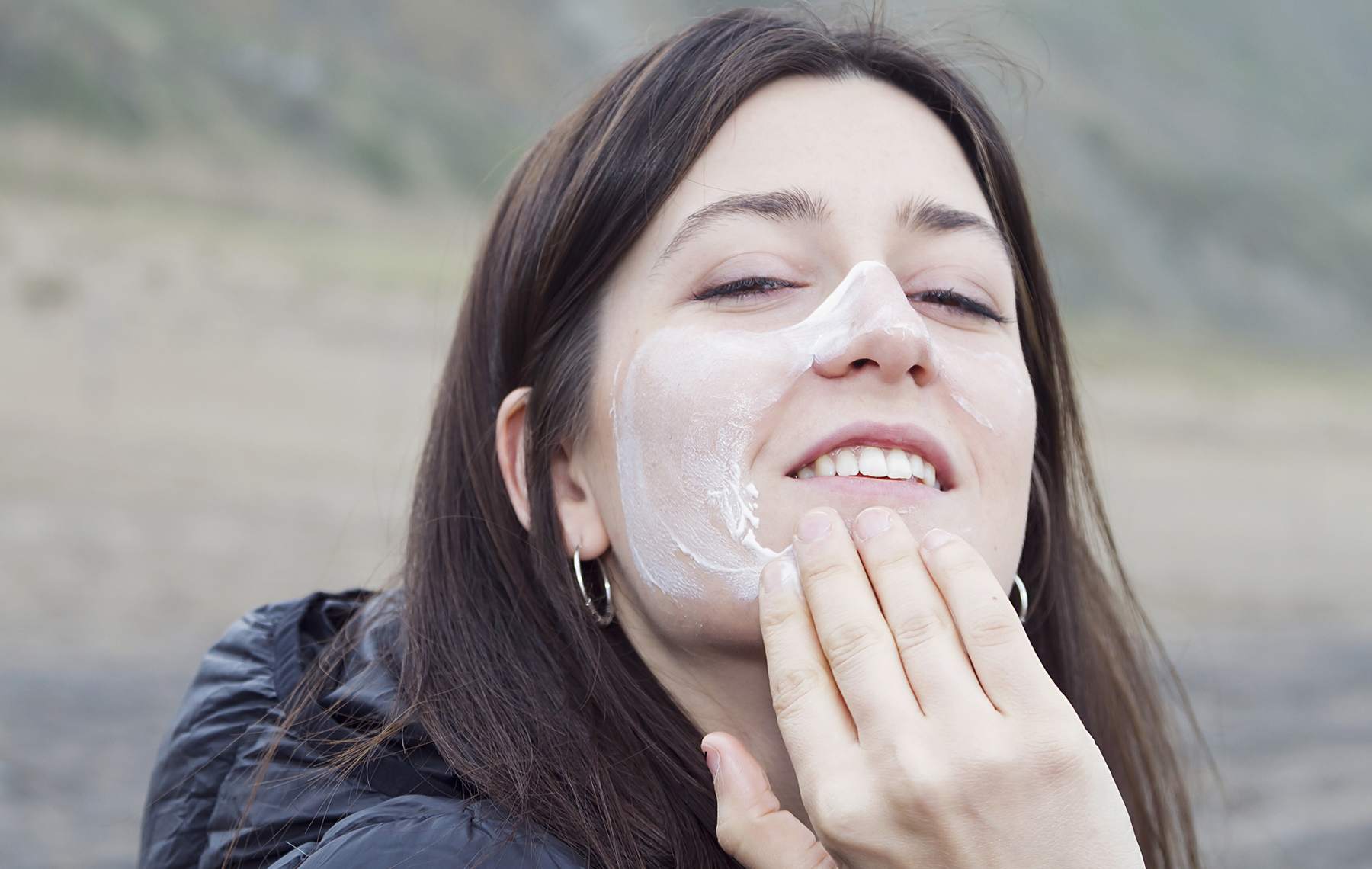 Young Woman Applying Cream On Her Face