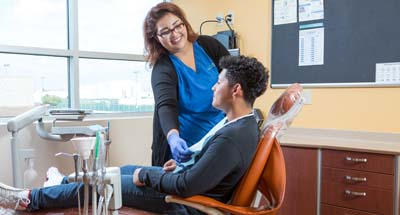 Dental assistant with patient in chair