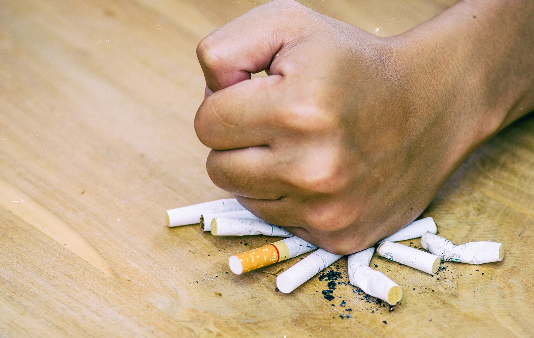 Male hand destroying cigarettes