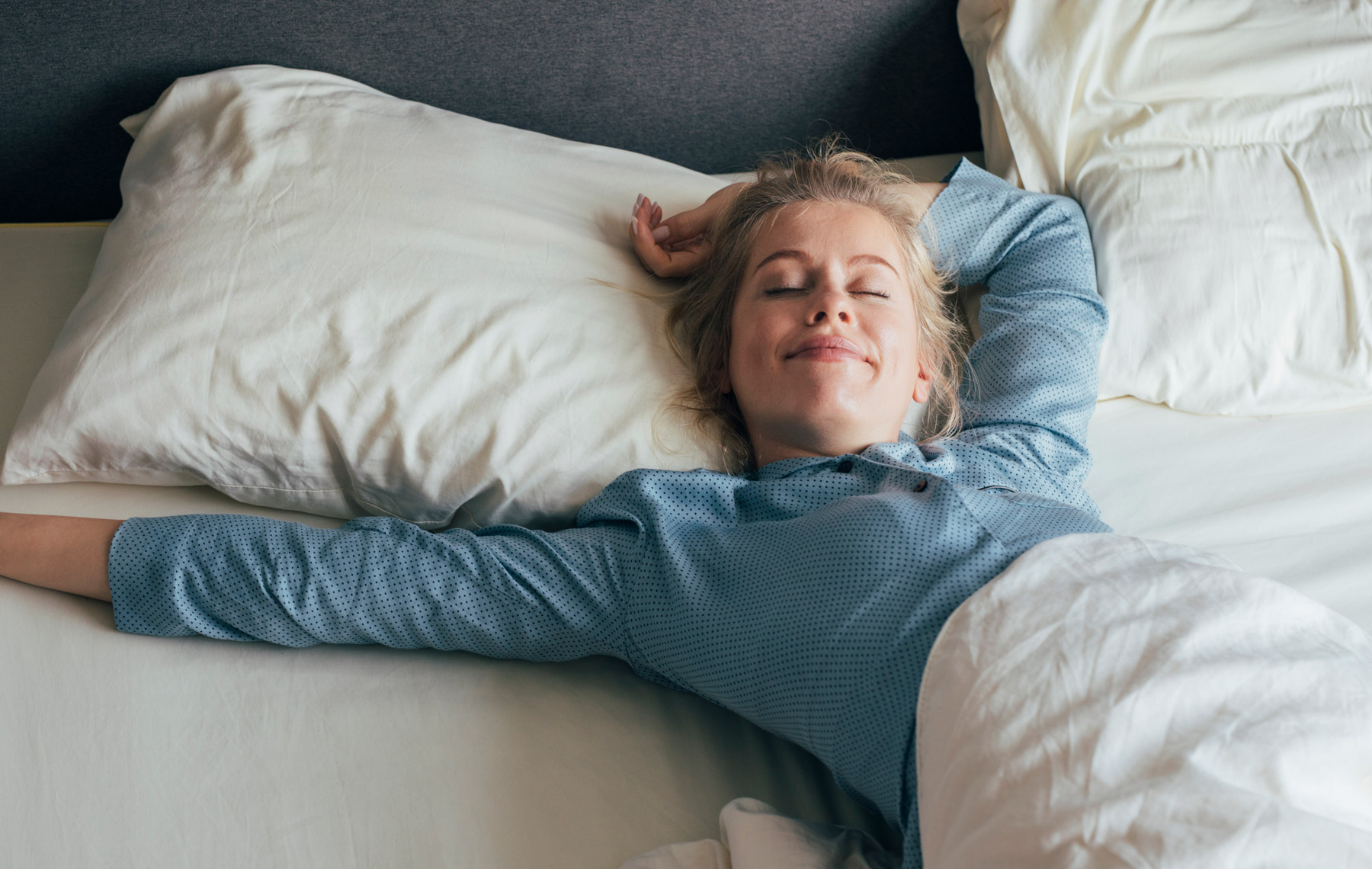 happy blonde woman in pyjamas stretches in bed after waking up in the mornin-early bird vs night owl