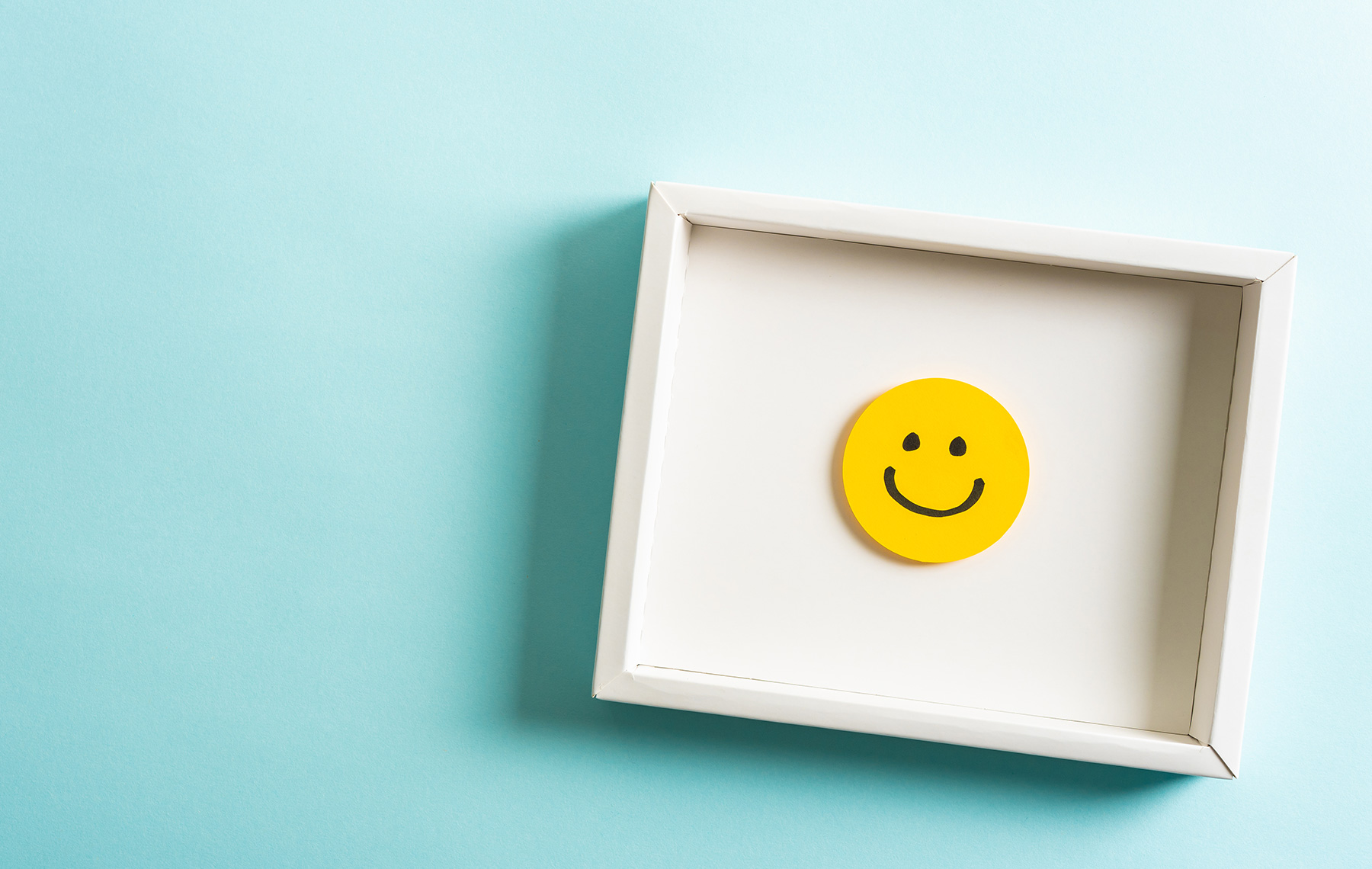 Happy yellow smiling emoticon face frame hanging on blue background with empty space for text fomo blog