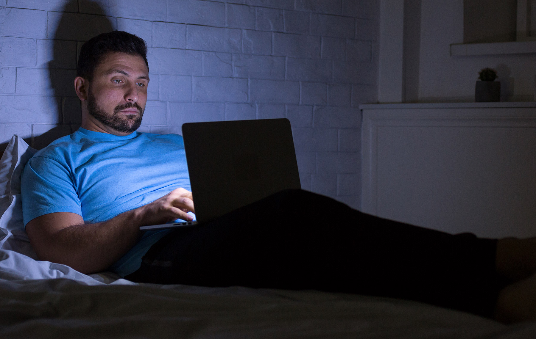 man chatting on laptop in bed instead of sleeping-early bird vs night owl