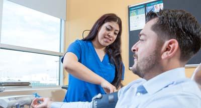 Nurse taking blood pressure of patient
