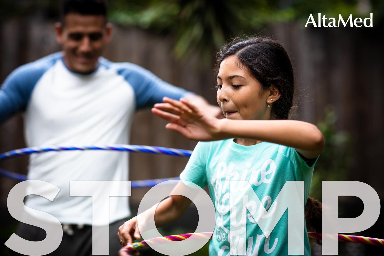Niña y su padre jugando hula hula en el jardín