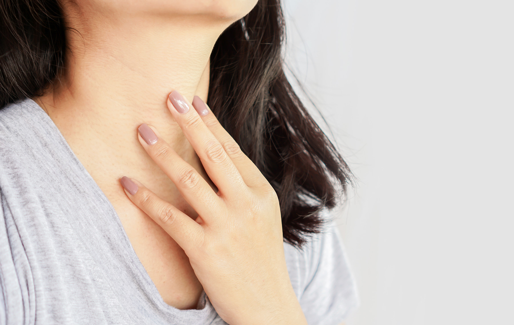 woman hand self checking thyroid gland on her neck